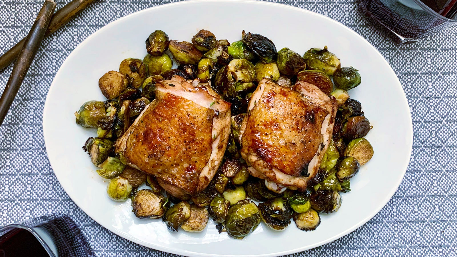 Two crispy-skinned chicken thighs on a white plate with balsamic-roasted brussels sprouts