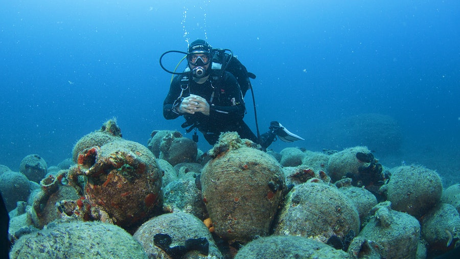 A diver and amphorae underwater