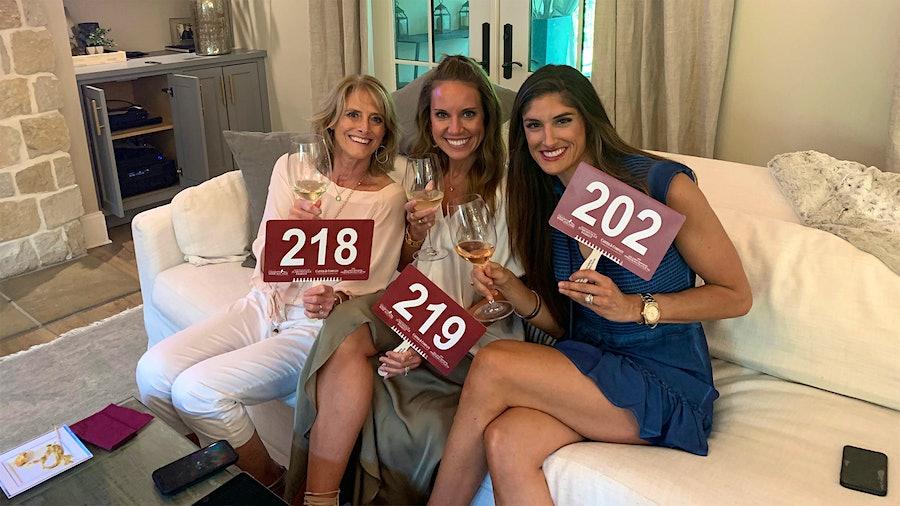 翡翠海岸投标人珍妮·戴利,劳伦Vlahos和蒂芙尼·爱德华兹,从左到右,观看和在线拍卖沙发上竞价。