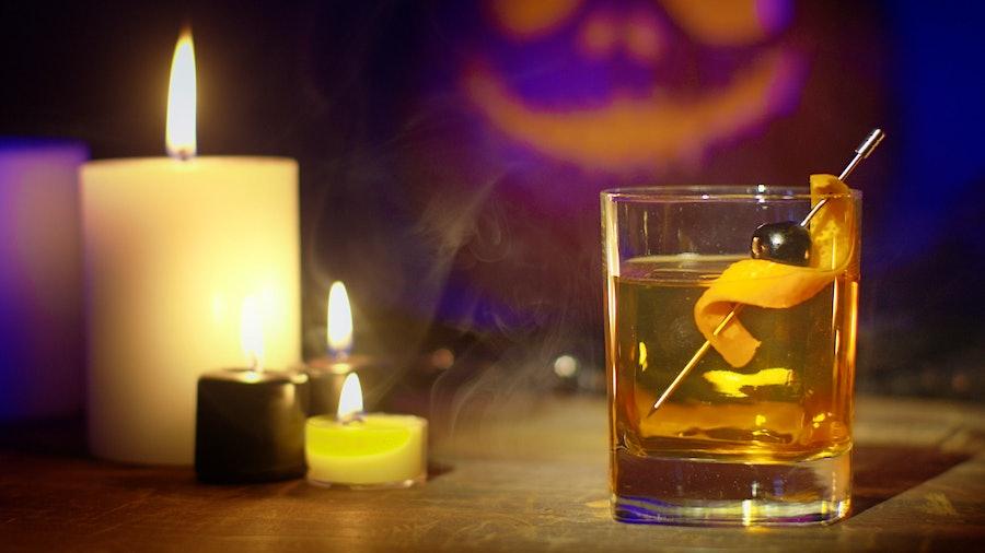 在蜡烛的一个怪异的设置枫叶波旁威士忌鸡尾酒和一个南瓜雕刻