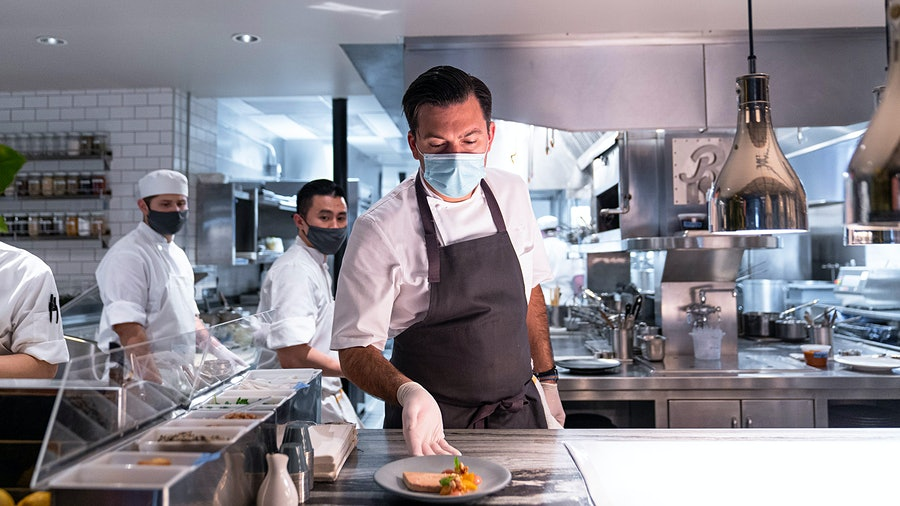 Chef Aaron Bludorn expedites in the kitchen of his eponymous Houston restaurant. He's happy to give diners good food while making them feel safe.