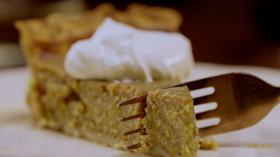 A fork slicing through pumpkin pie topped with whipped cream