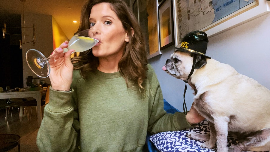 Cassia Schifter sips a French 75 next to her dog, Puggsy
