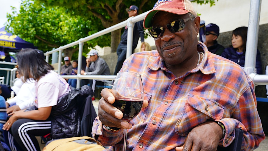 Dusty Baker takes in a college game with a glass of his own wine.