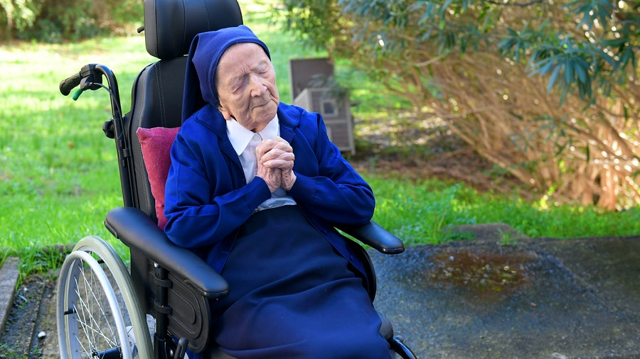 Sister André prays before celebrating her 117th birthday.