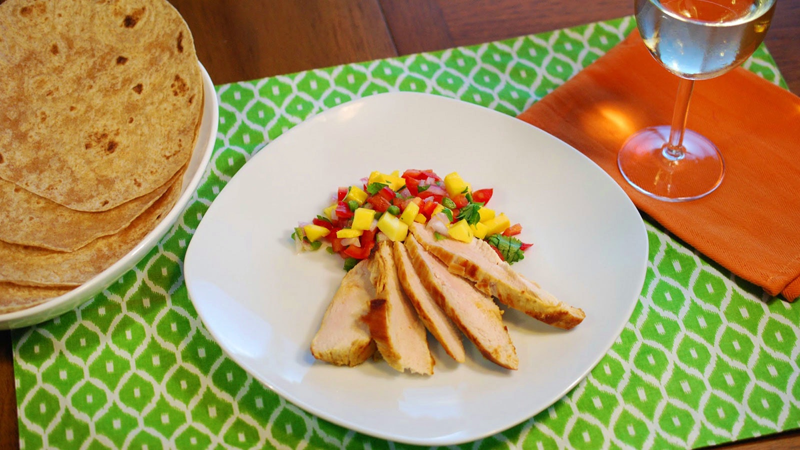 A white plate with sliced chicken breast and mango salsa, a plate with tortillas and a glass of white wine