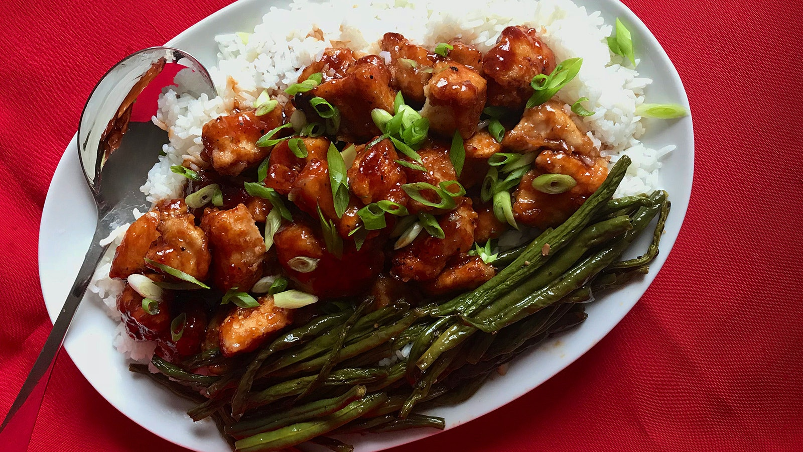 Plate of crispy chicken in a sweet-sour-spicy sauce, with white rice and roasted green beans