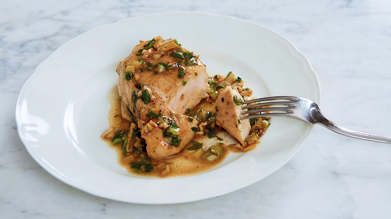 A white plate with a boneless chicken breast topped with an oil-based sauce of garlic, parsley and scallions.