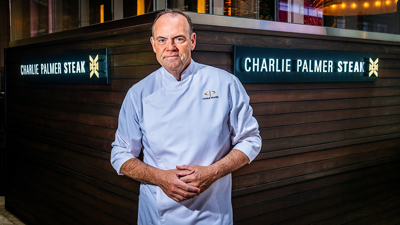 Chef Charlie Palmer in his chef coat in front of the signage at Charlie Palmer Steak NYC