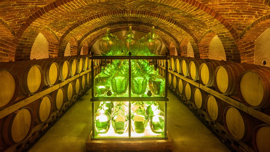 A cellar with barrels and glass wine bottles