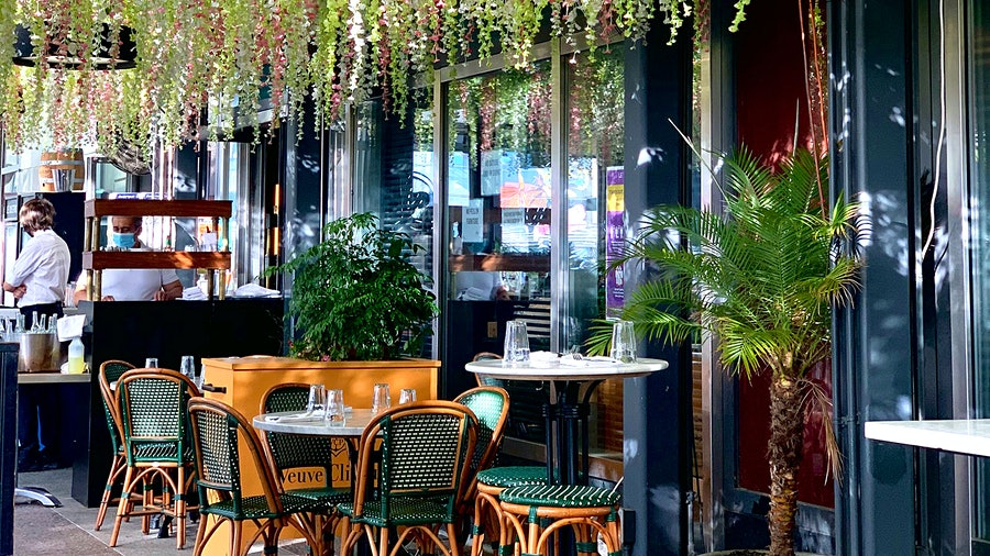 Suspended plants add a welcoming feel to the outdoor tables at Le District's Liberty Bistro.