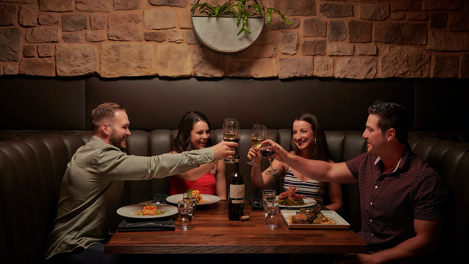Four friends cheers their wine glasses at a booth in Mason Bar and Kitchen