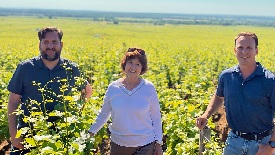 Evenstad Estates' winemaking and viticulture vice president Michael Fay, left, owner and founder Grace Evenstad and CEO/President Ryan Harris stand in Burgundy's Bonnes Mares vineyard.