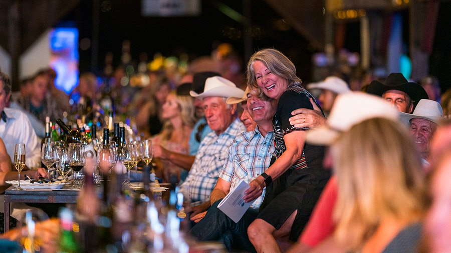 Friends and vintners Karen Cakebread and John Truchard embrace during the Harvest Stomp wine auction.