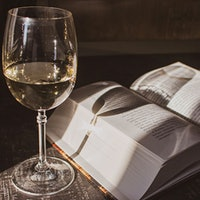 Glass of white wine on a table next to an open bookHow Do You Spell that Wine Word?